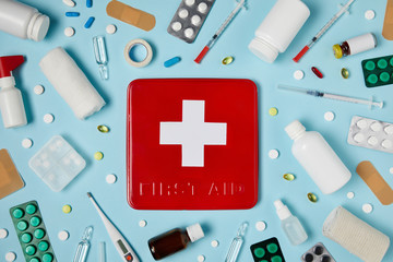 top view of red first aid kit box on blue surface surrounded with different medicines