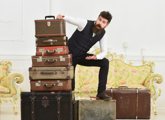 Man, butler with beard and mustache delivers luggage, luxury white interior background. Macho elegant on shocked face standing near pile of vintage suitcase. Luggage and travelling concept.