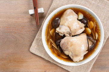steamed chicken thigh with soy sauce in a ceramic dish on wooden table, top view. homemade style food concept.