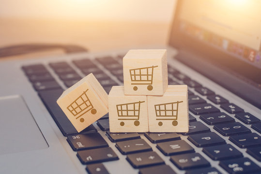 Buy online concept with trolley on wooden cubes on a keyboard of laptop