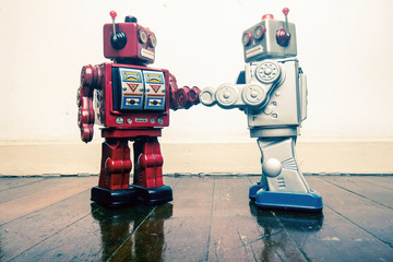 two vintage robot shake hands on a old wooden floor