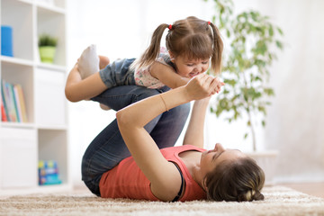 love and family concept - happy mom and child daughter having fun pastime at home