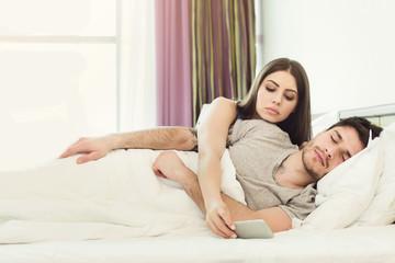Jealous wife spying phone of husband while man sleeping - fototapety na wymiar
