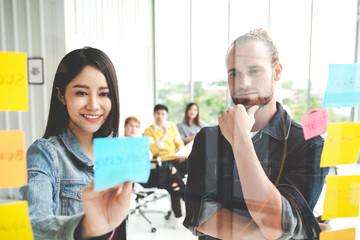 Group of young successful creative multiethnic team smile and brainstorm on project together in modern office. Woman sticking and look at sticky note on glass wall sharing idea with engaged cheerful.
