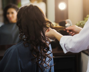 Hairdresser making curly hair to client