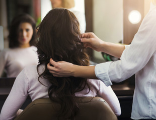 Hairdresser making curly hair to woman