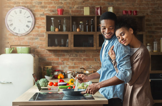 Loving black wife and husband preparing dinner in kitchen