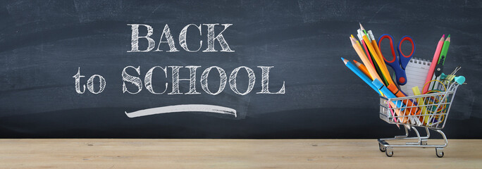 Banner of Shopping cart with school supply in front of blackboard. Back to school concept.
