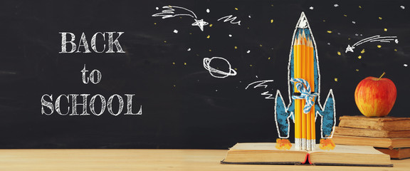 Back to school banner. rocket sketch and pencils over open book in front of classroom blackboard.