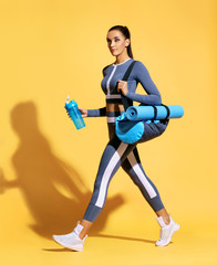 Go to gym! Attractive latin woman in fashionable sportswear on yellow background. Dynamic movement. Side view. Sports and healthy lifestyle