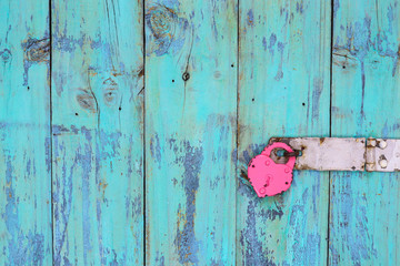 Iron heart lock hanging on antique rustic teal blue door; old wooden background with love concept and copy space