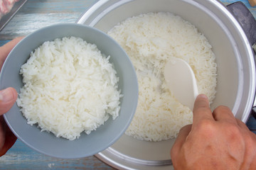 Cooked rice on plastic ladle in electric rice cooker