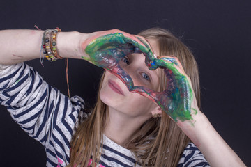 Beautiful blond young girl with freckles and hands painted in colorful paints indoors on black background, closeup portrait