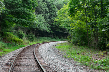 Train tracks lead into a curve or bend in the forest of West Virginia.