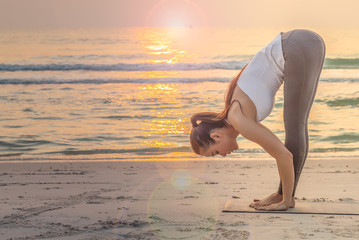 Young sport girl doing Yoga pose on the beach in the morning.