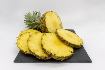 sliced pineapple served on a slate board