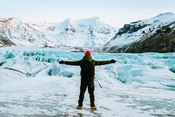 Tuinposter Gletsjers adventurous man walking on a glacier in iceland
