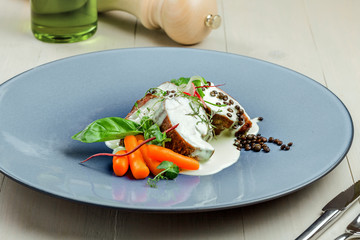 Delicious meat steak medallions with cream sauce on a luxurious plate. Healthy food made of meat fillet and fresh herbs on a white wooden table.