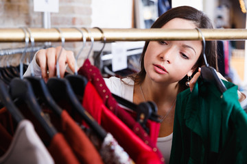 Portrait of woman customer choosing shirt  in the  store