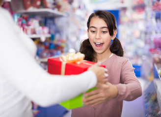 Portrait of small girl receives  gifts with emotio