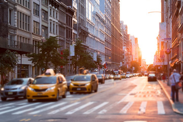 Poster New York TAXI Sunlight shines down a busy street in New York City with taxis stopped at the intersection