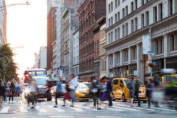 Busy people in motion across an intersection on Broadway in Manhattan New York City