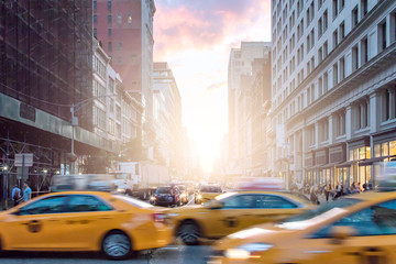 Taxi cabs in motion past crowds of people on Broadway with a colorful sunset in Manhattan New York City