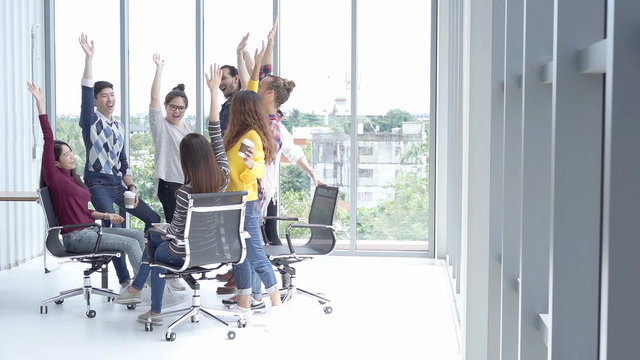 Happy Multi Ethnic Creative raise hands together at the office,Multi Ethnic and Teamwork Concept