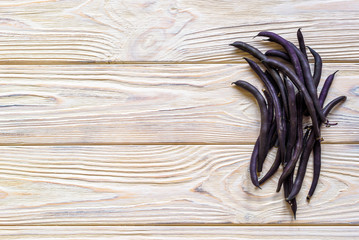 Beans of purple beans on a wooden background. Spinach beans. Asparagus beans