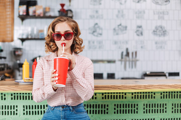 Beautiful lady in sunglasses and shirt sitting at the bar counter and drinking soda water in cafe