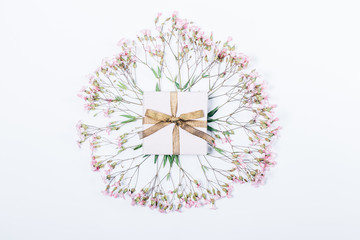 Tiny gift box in the center of circle of gypsophila pink flowers