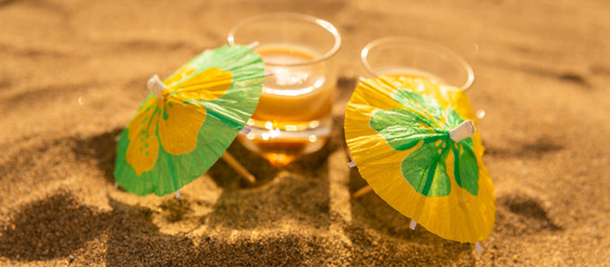 colorful shots drinks on a sandy beach with umbrellas for drinks