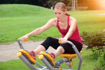 Sportliche Frau bei Fitness, Training, Sport und Workout an Trainigsgerät für Kraftsport mit Park
