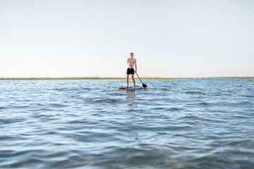 Man paddleboarding on the lake during the morning light, wide landscape view with blue water and sky