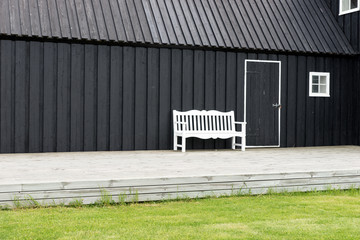 White bench in front of black wooden house in Iceland