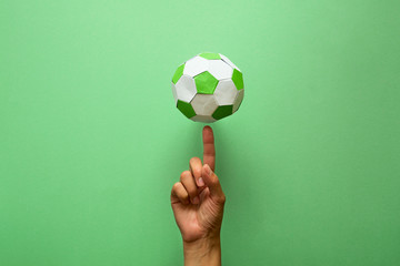 Paper soccer ball on soccer field or green background. Origami. Paper craft. Soccer game concept.