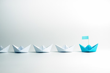 Leadership concept. Blue leader paper ship leading among white on white background.