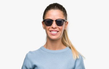 Beautiful young woman wearing sunglasses and ponytail with a happy face standing and smiling with a confident smile showing teeth