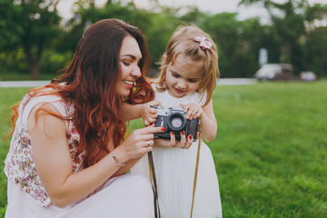 Smiling woman in light dress and little cute child baby girl holding retro vintage photo camera in green park. Mother, little kid daughter. Mother's Day, love family, parenthood, childhood concept.