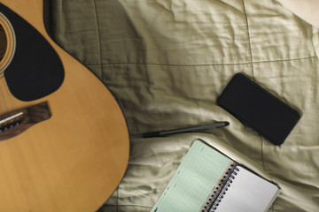 Flat lay of smartphone, notepad, pen, and guitar on  bed