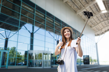 Young traveler tourist woman with retro vintage photo camera show thumb up doing selfie on mobile phone with monopod selfish stick at airport.Passenger traveling abroad on weekend. Air flight concept.