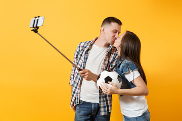 Kiss couple, woman man, football fans doing selfie on mobile phone with monopod selfish stick, cheer up support team, soccer ball isolated on yellow background. Sport family leisure lifestyle concept