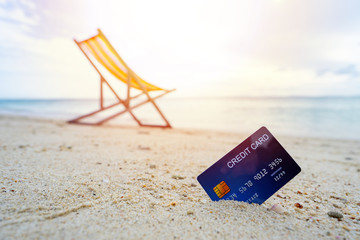 Blue credit card paying for holiday trip, wooden comfortable chair on the beach and beautiful sea, copy space.