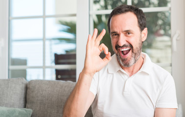 Handsome middle age man doing ok sign with fingers, excellent symbol
