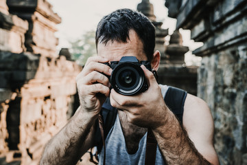 Handsome young tourist feeling the peace and taking some pictures of the great Borobudur temple, historical famous place in the java island Indonesia. Lifestyle and travel photography.