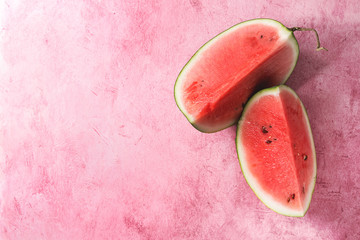 Ripe sliced watermelon over pink texture background. Flat lay, space.