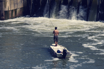A man in a boat fishing near the dam