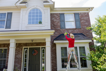 Man washing the soffits or eaves of a modern house