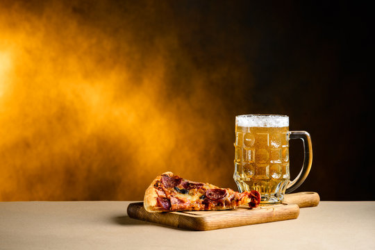Slice of delicious homemade pizza served with light cold beer on