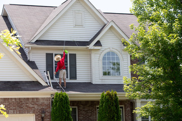 Homeowner washing the exterior of his house